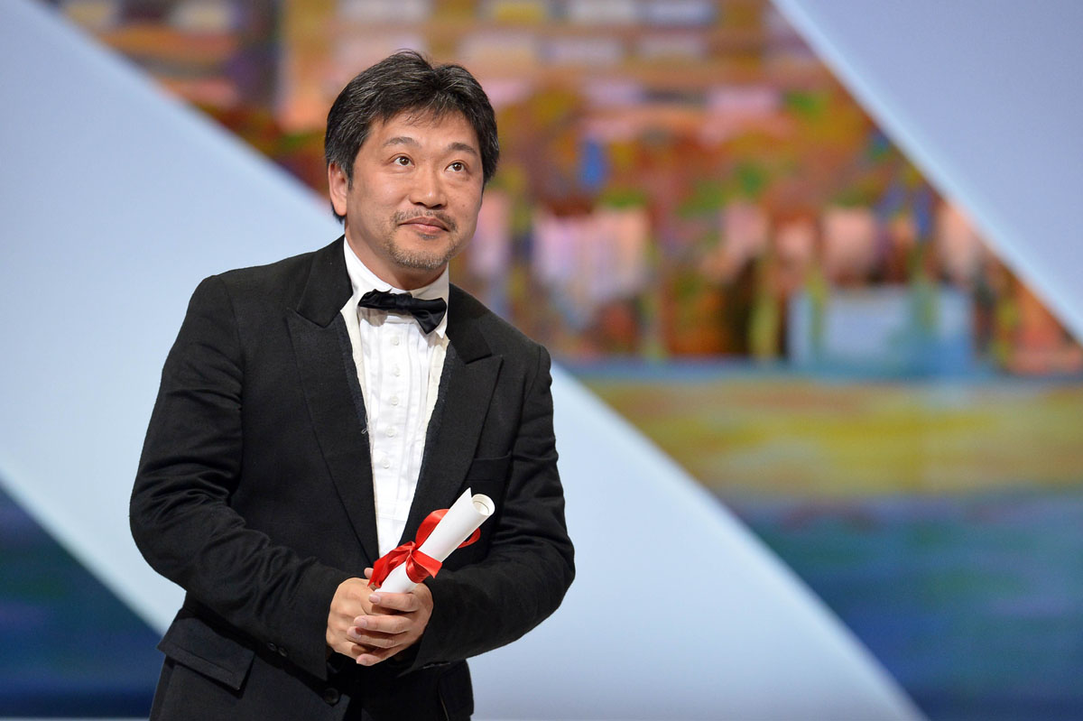 "Japanese director Hirokazu Kore-Eda poses on stage on May 26, 2013 after being awarded with the Prix du Jury (Jury's Prize) for the film ""Like Father, Like Son"" during the closing ceremony of the 66th Cannes film festival in Cannes. AFP PHOTO / ALBERTO PIZZOLI"