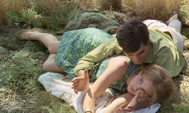 Francoise and Therese lie in the grass together, he leaning over her in an embrace. Therese is wearing a 60s blue floral shift dress and has straight blonde hair, he is dark haired and wears a pale green shirt and white slacks.